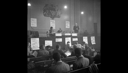 Black and white photograph showing Amy Ashwood Garvey chairing a session alongside John McNair at the Manchester Pan-African Congress in 1945. Anti-colonial signs are posted on the stage and delegates sit on benches.