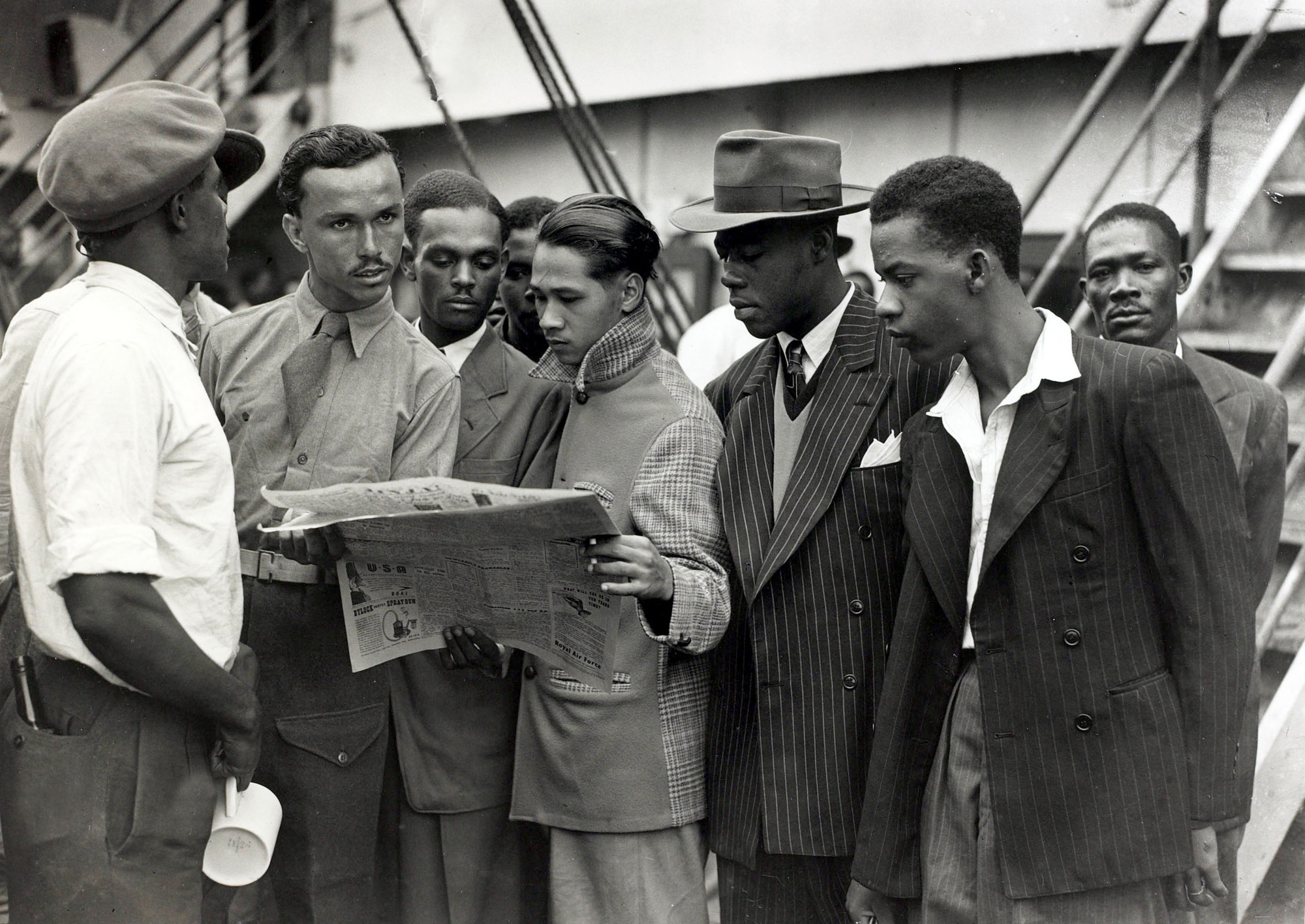 Black and white photograph of a group of Caribbean men reading a newspaper at Tilbury docks
