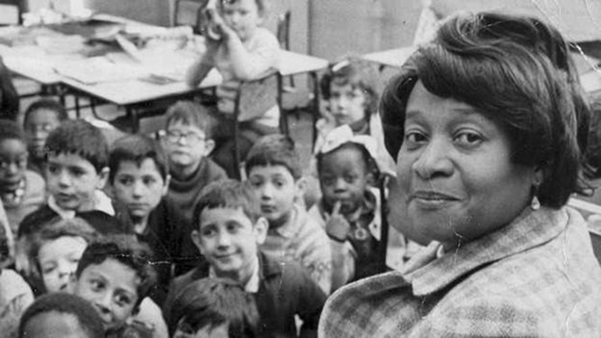 Black and white photograph of Beryl Gilroy with primary school pupils in a classroom