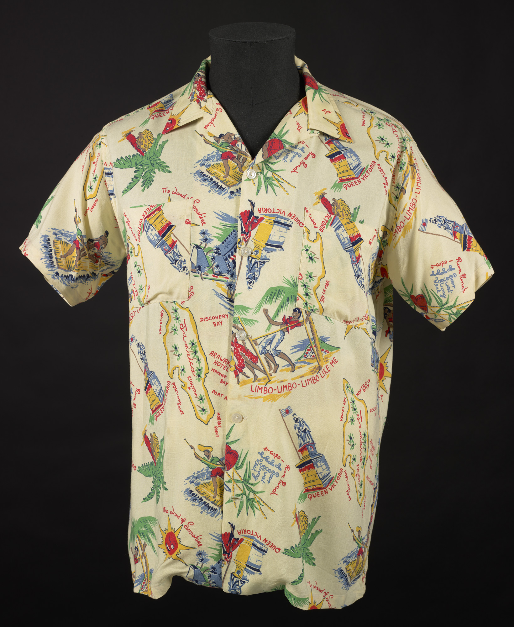 Photograph of the front of Winston Levy's 'Jamaica' shirt, pale yellow with a coloured print depicting the island and certain landmarks
