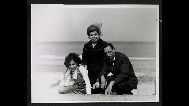 Black and white photograph of Andrea Levy on holiday as a child with her mother and father, sitting on a beach