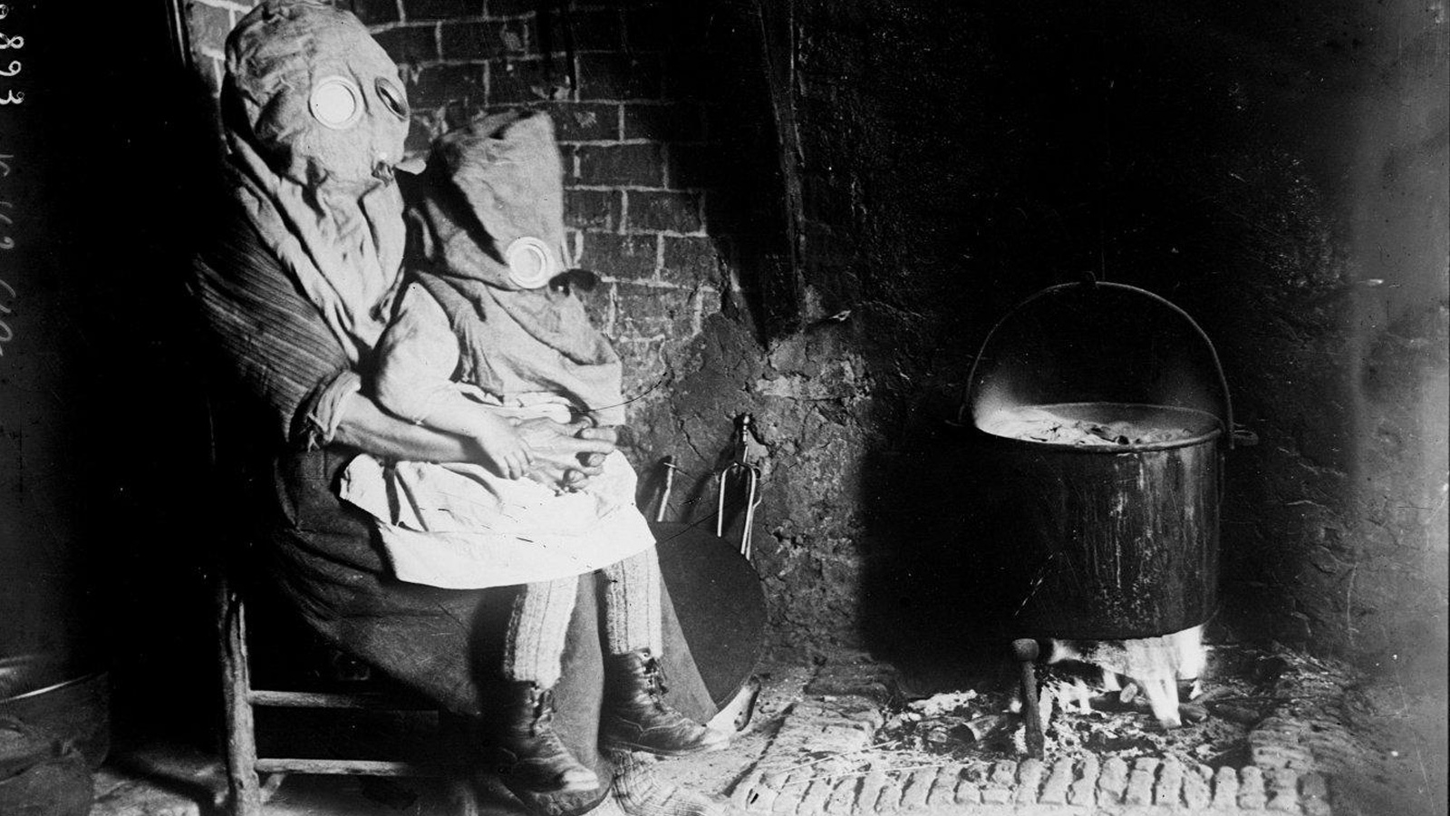 Banner for civilian article. A photograph shows a mother holding her small child in their home. They are both wearing gas masks. To their right is a pot on an open fire.