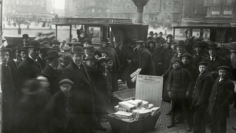 Banner for Civilians article. A black and white photograph taken in Copenhagen, Denmark. A crowd is pictured surrounding baskets of produce in a main square. Traffic can be seen behind them.