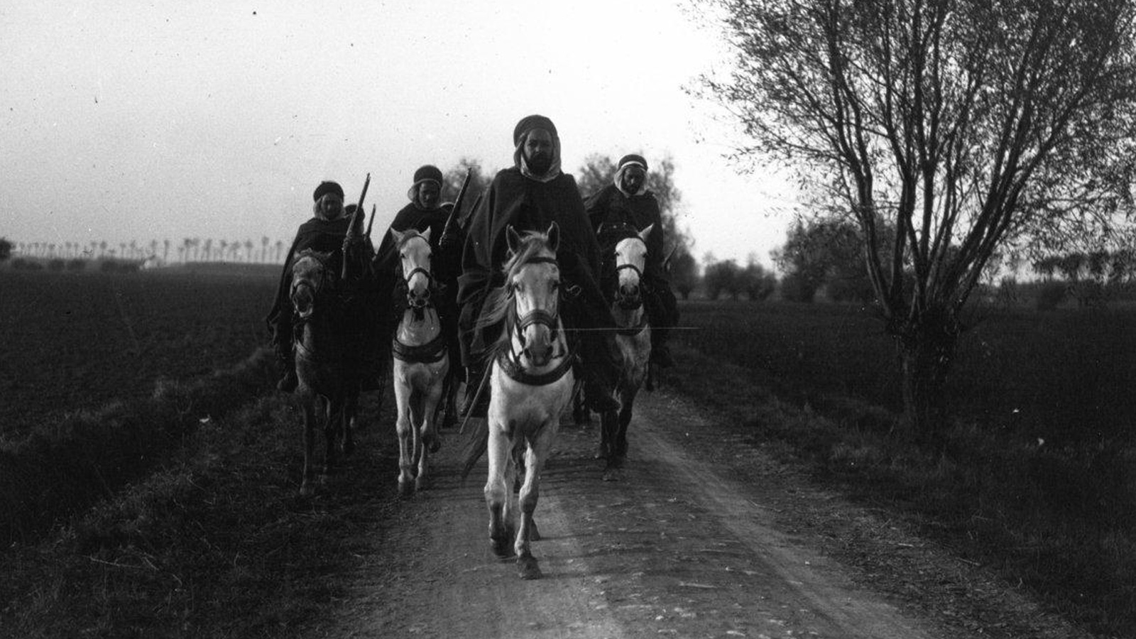 Banner for colonial troops article. 4 soldiers feature in a black and white photograph. They are cantering along a road on horses, they are wearing Sudanese style dress and some have rifles on their backs.