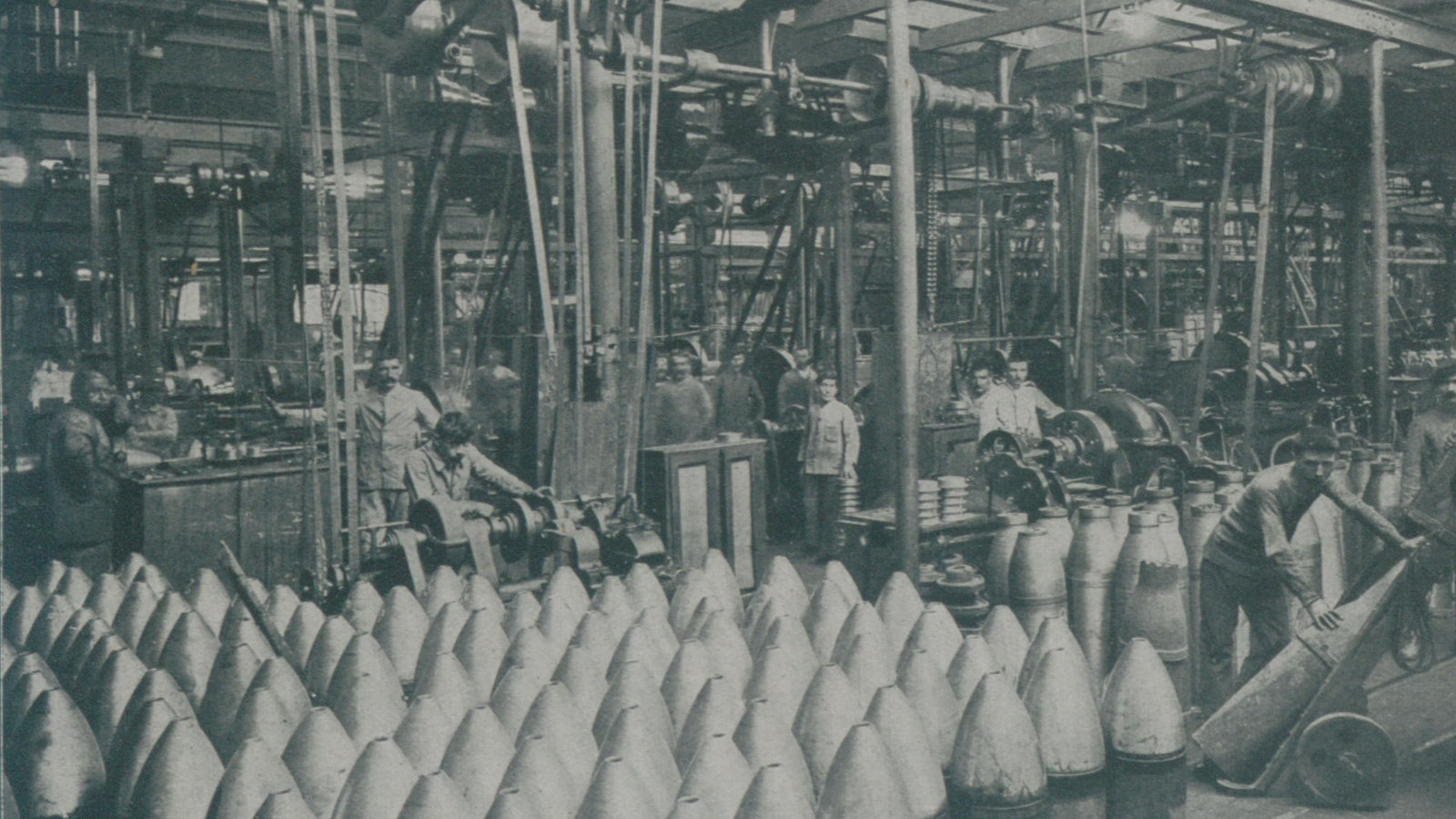 A photograph a munitions plant. Shell are lining the aisles, workers can be seen behind them standing at various machines.