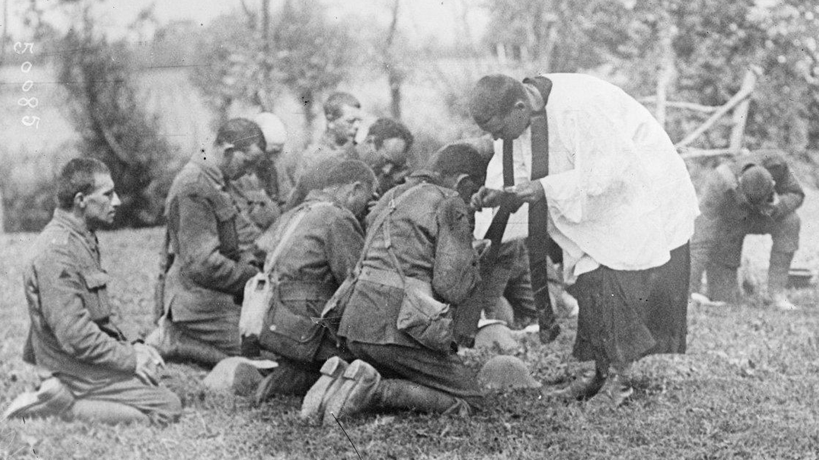Faith article. Black and white photograph showing 5 soldiers praying with a priest in an open field.
