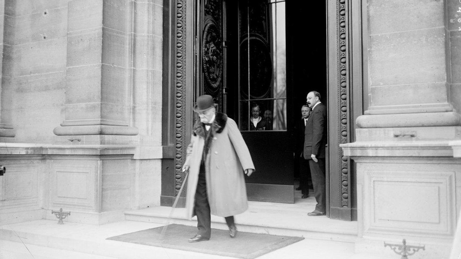Banner showing man leaving a building. Large wooden doors stand behind him.
