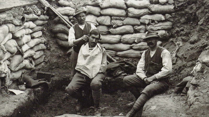 banner showing men receiving a hair cut and shave whilst sat in a trench. They are surrounded by sand bags.