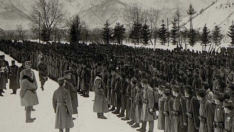 Photograph of snowy surroundings, a regiment is being addressed by their leader.