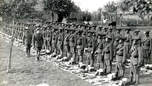 Regiment lining up for inspection, kit bags lay at their feet.