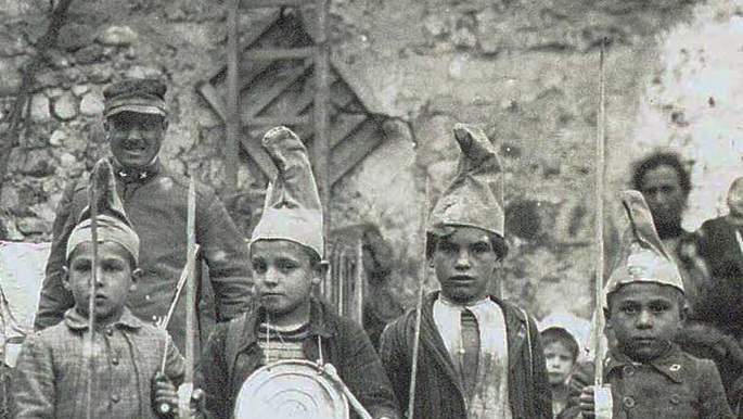 Banner showing children dressed as soldiers. Photograph.
