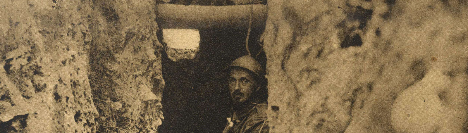 Lone man sat deep inside a dug-out within a trench.
