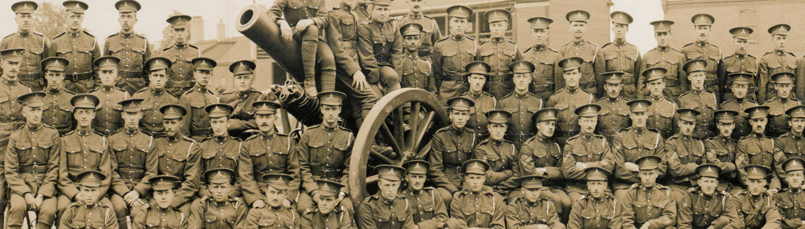 Battalion photograph. Men are lined up like in school or class photographs - some are sat on large artillery.