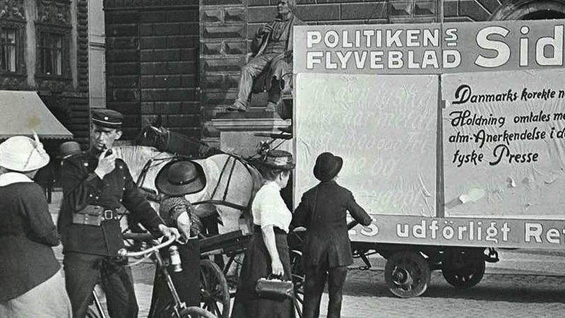 Children, police man and women upon bicycles reading a large sign hauled by a horse