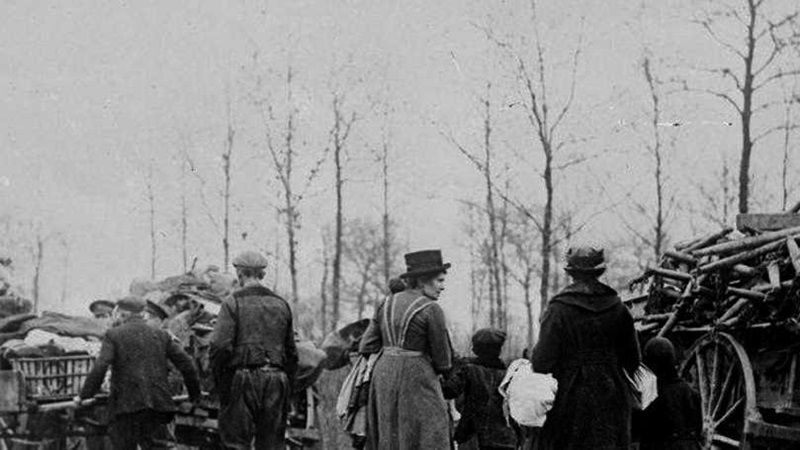 Photograph of French refugees moving down a road, with horse drawn carts carrying their belongings