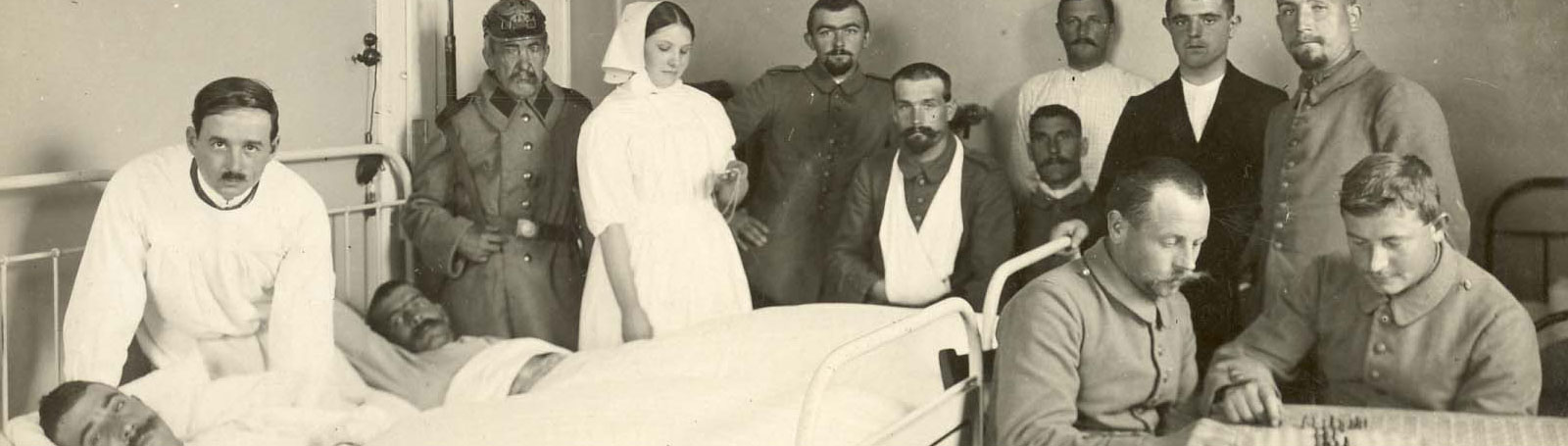 Photograph of crowded hospital ward with patients, doctors, orderlies and nurses.