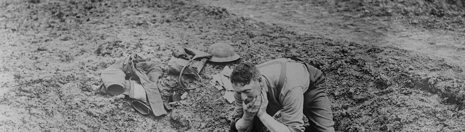 Photograph of man kneeling in mud
