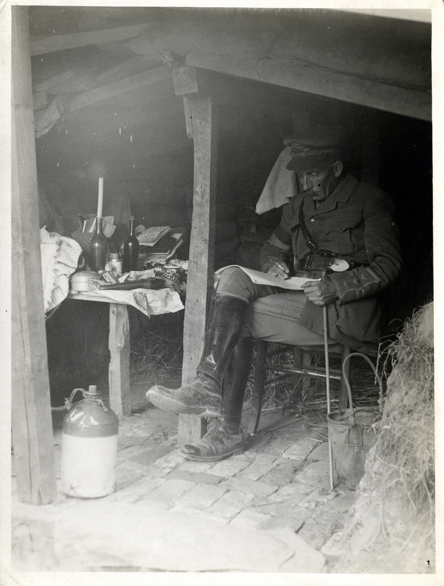 A British officer in his hut dug into the side of a trench, 1915. The hut has walls reinforced with sandbags, hay bales to protect against shell attacks, and a brick floor.