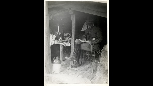 Photograph of a British officer sat in his hut dug into the side of a trench, 1915. The hut has walls reinforced with sandbags, hay bales to protect against shell attacks, and a brick floor.
