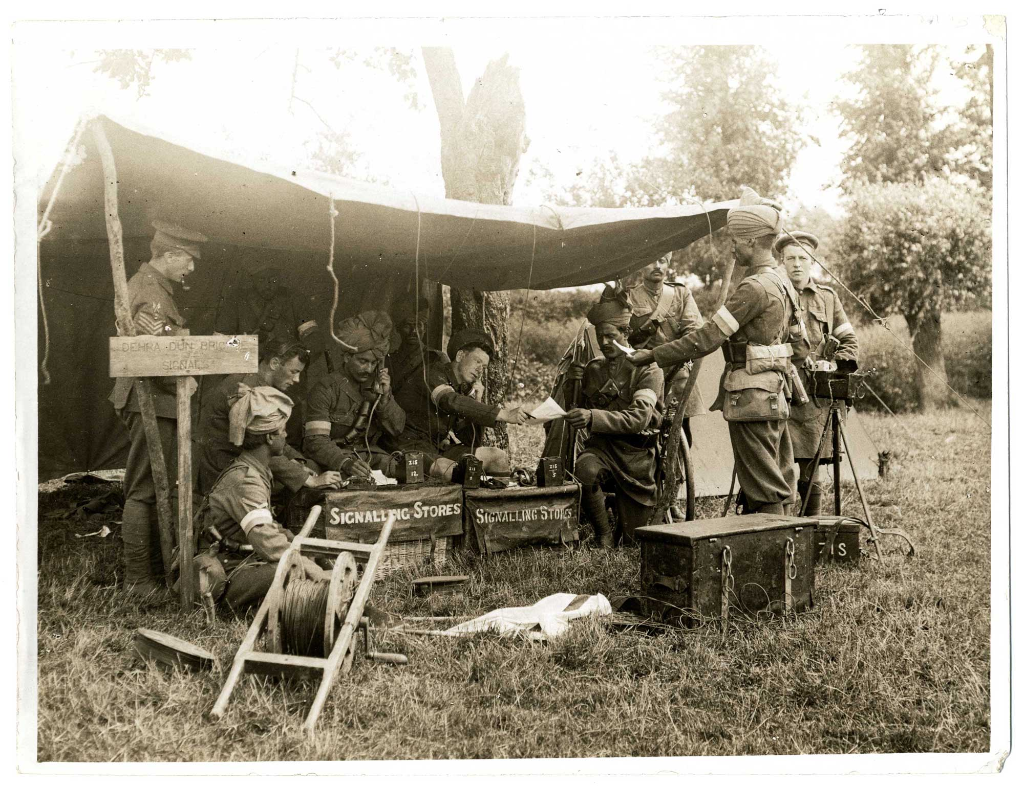 A group of soldiers at a signal station for the Dehra Dun Brigade in 1915. The two men in the centre of the picture are on field telephones, taking messages.