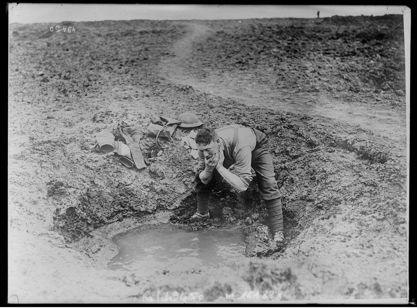 British soldier washing in the stagnant water that has collected in a shell crater, 1917.