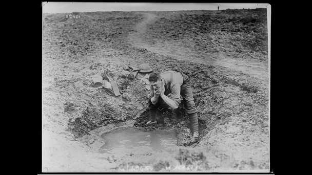 Photograph of British soldier washing in the stagnant water that has collected in a shell crater, 1917.