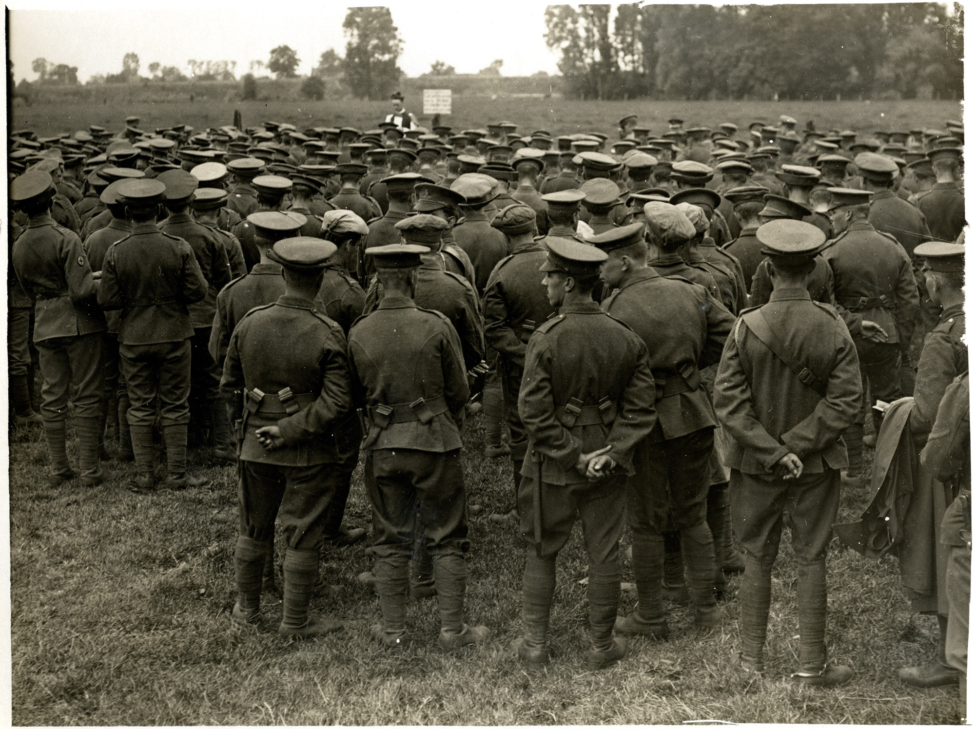 Photograph, 1915, showing a large group of soldiers attending a church service in a field. The priest can be seen in the middle of the picture towards the back.