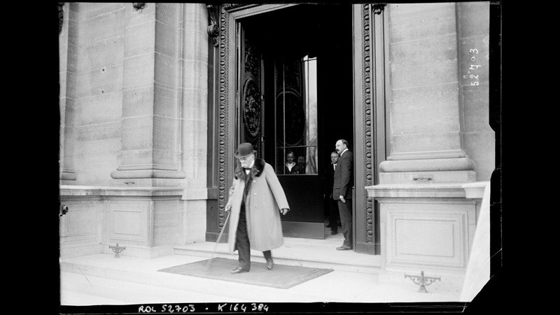 Photograph of Georges Clémenceau leaving the Peace Conference, walking out of a building's entrance. Other figures stand in the doorway
