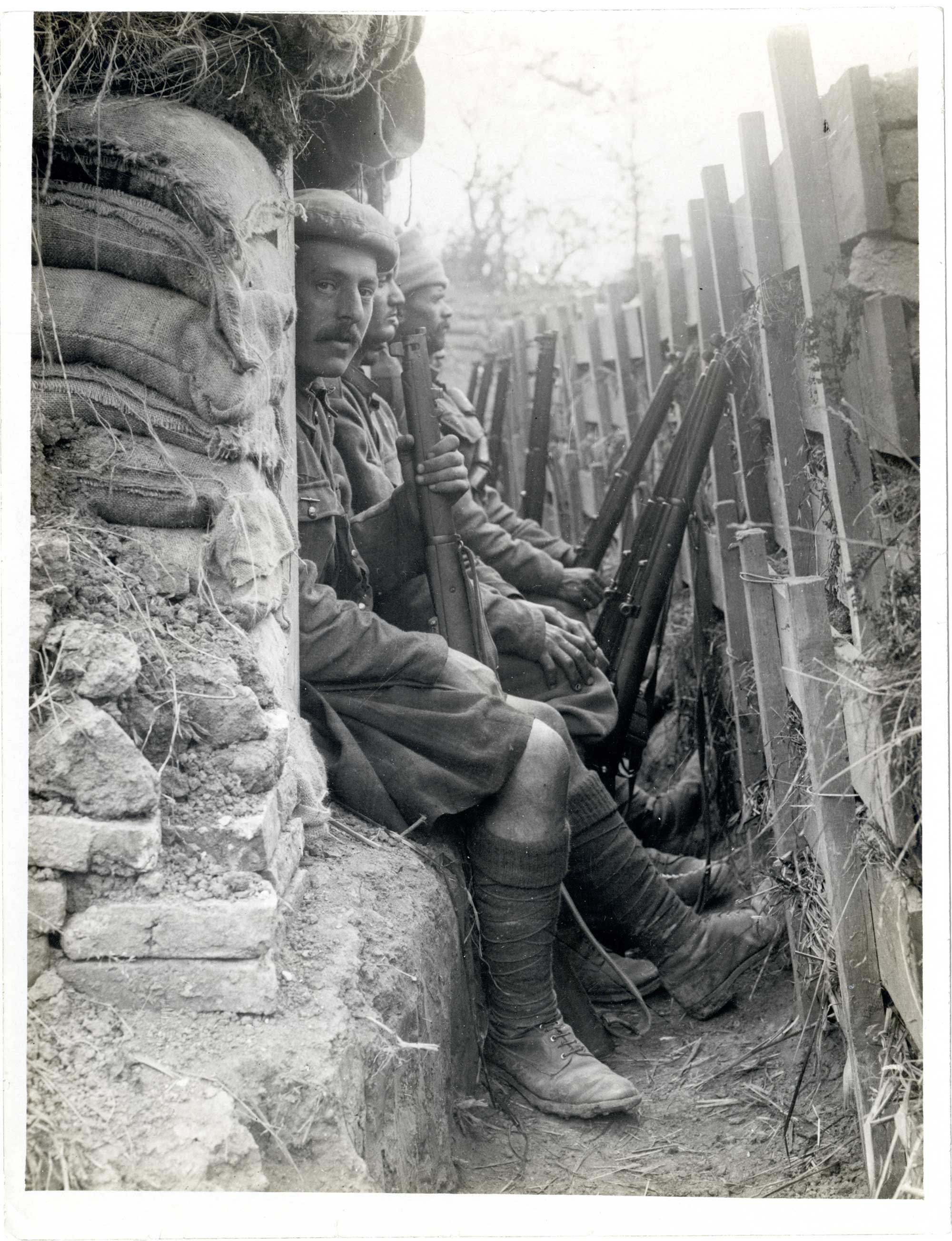 Photograph showing a group of soldiers, Highlander and Indian Dogras, sitting in a trench. Each man has a rifle in front of him, to which a bayonet could be fixed for close combat, 1915.