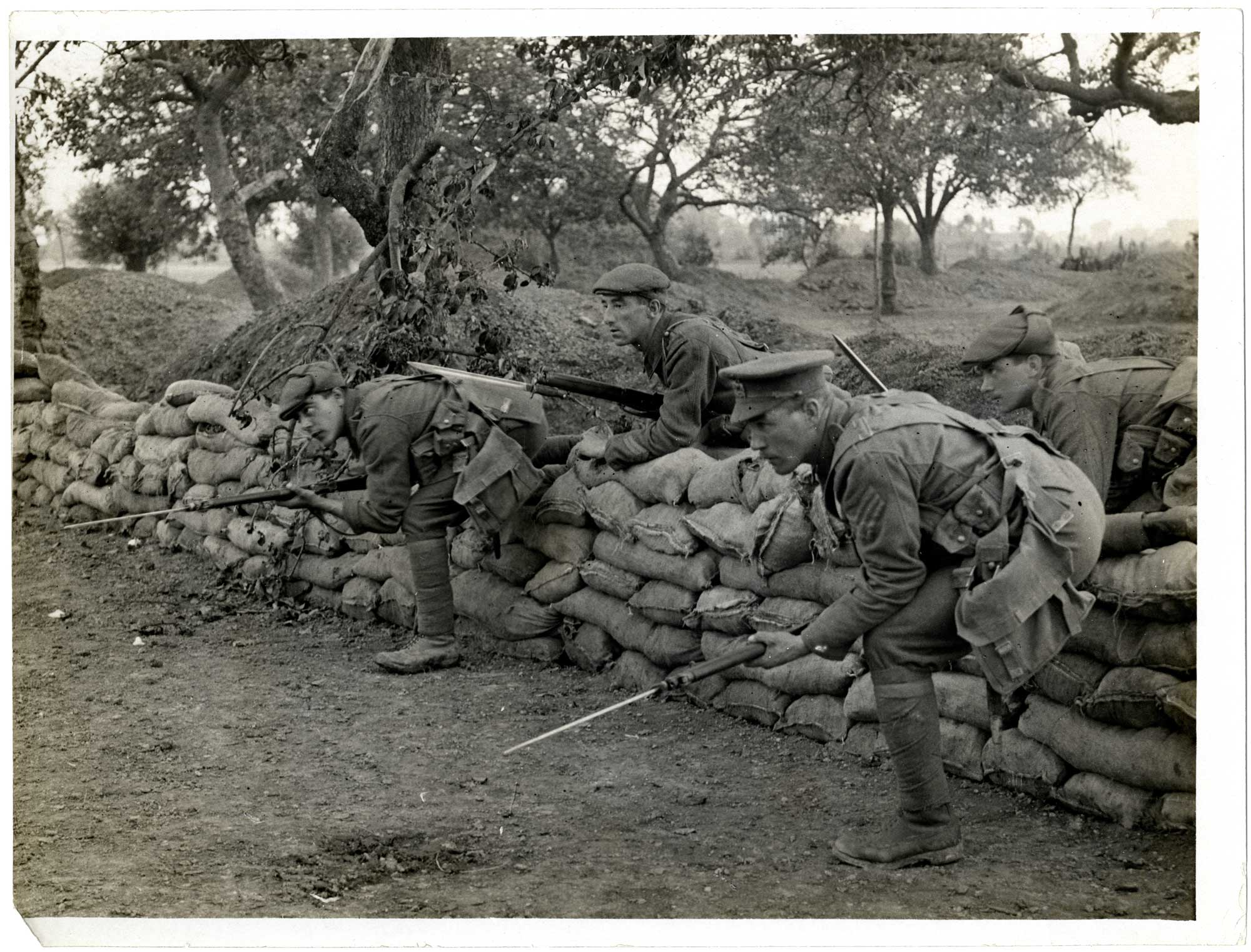 A photograph from 1914-15 of British troops leaving a shallow trench built up with sandbags, probably during a training exercise.