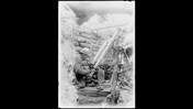 Photograph showing a French soldier in a front line trench, May 1917. He is firing a pneumatic trench mortar, an indirect fire weapon.