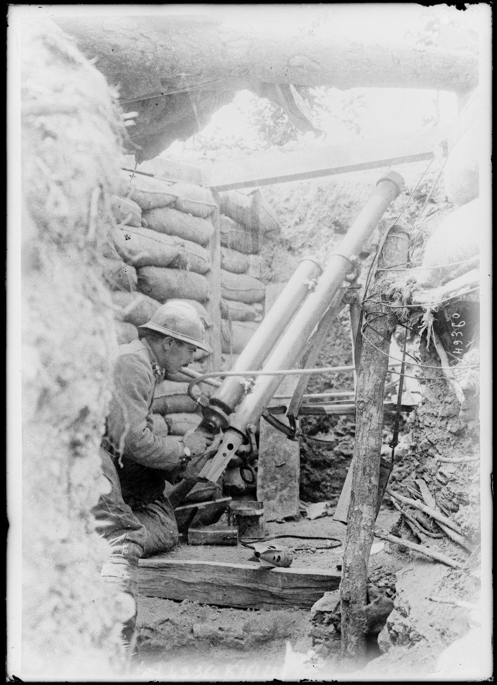 Photograph showing a French soldier in a front line trench, May 1917. He is firing a pneumatic trench mortar, an indirect fire weapon. This weapon was the counterpart of the German Minenwerfer, a short-range anti-trench weapon.