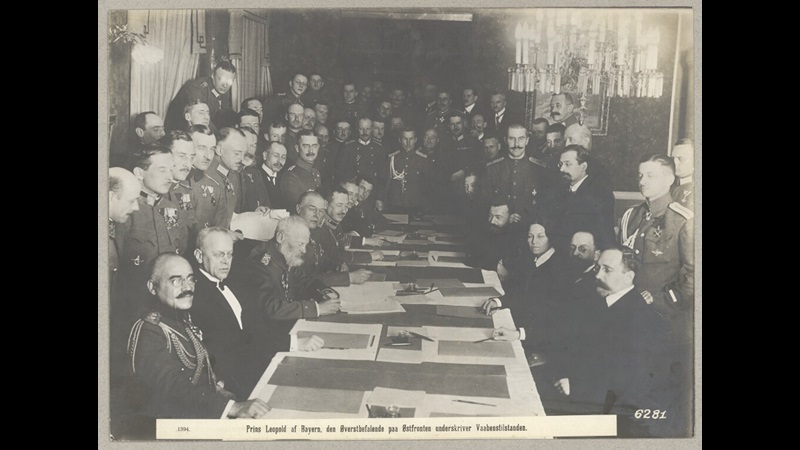 Photograph taken at Brest Litovsk, showing men seated around a table which is covered in papers