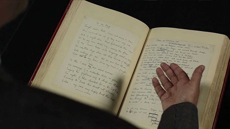 Film still of Dr Santanu Das's hand gesturing to the manuscript for Dulce et Decorum Est by Wilfred Owen