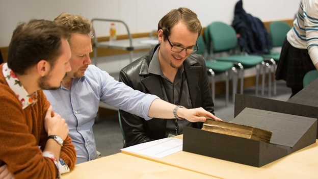 Three PhD placement students sitting at a table looking at a book from the British Library collection
