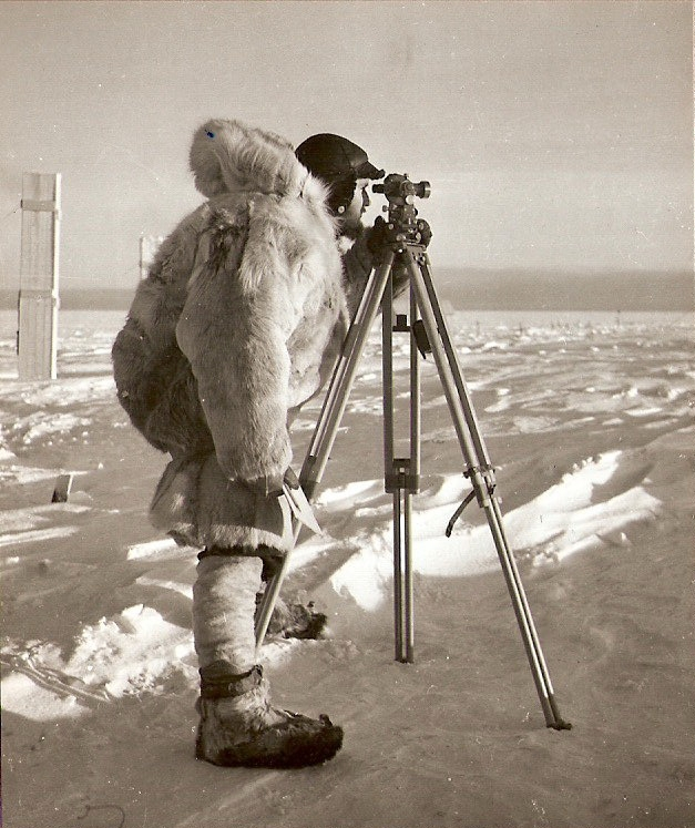 Photograph of Charles Swithinbank surveying stakes in an ice shelf