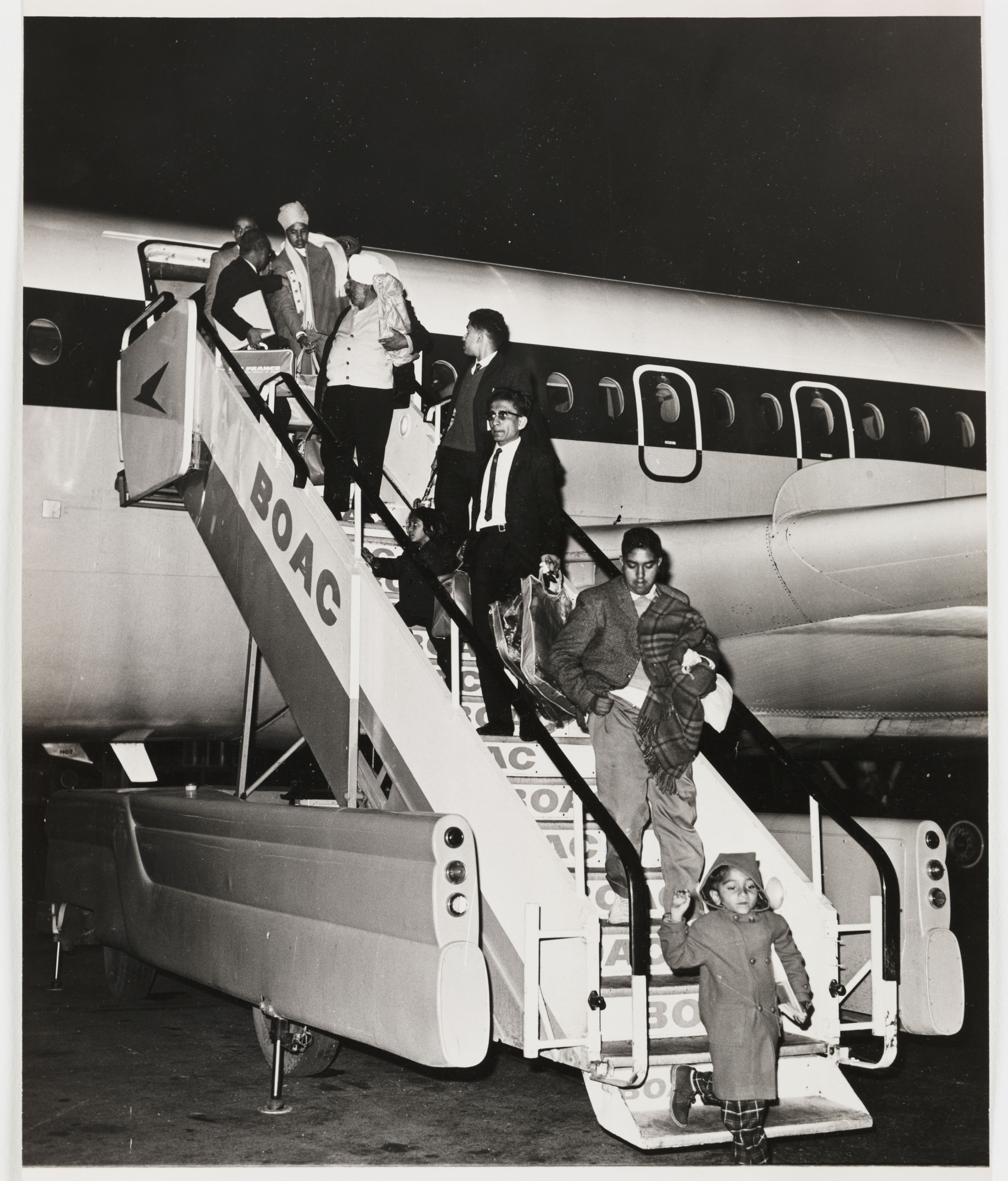 Black and white photograph of people leaving a plane. Image courtesy of Daily Herald Archive.