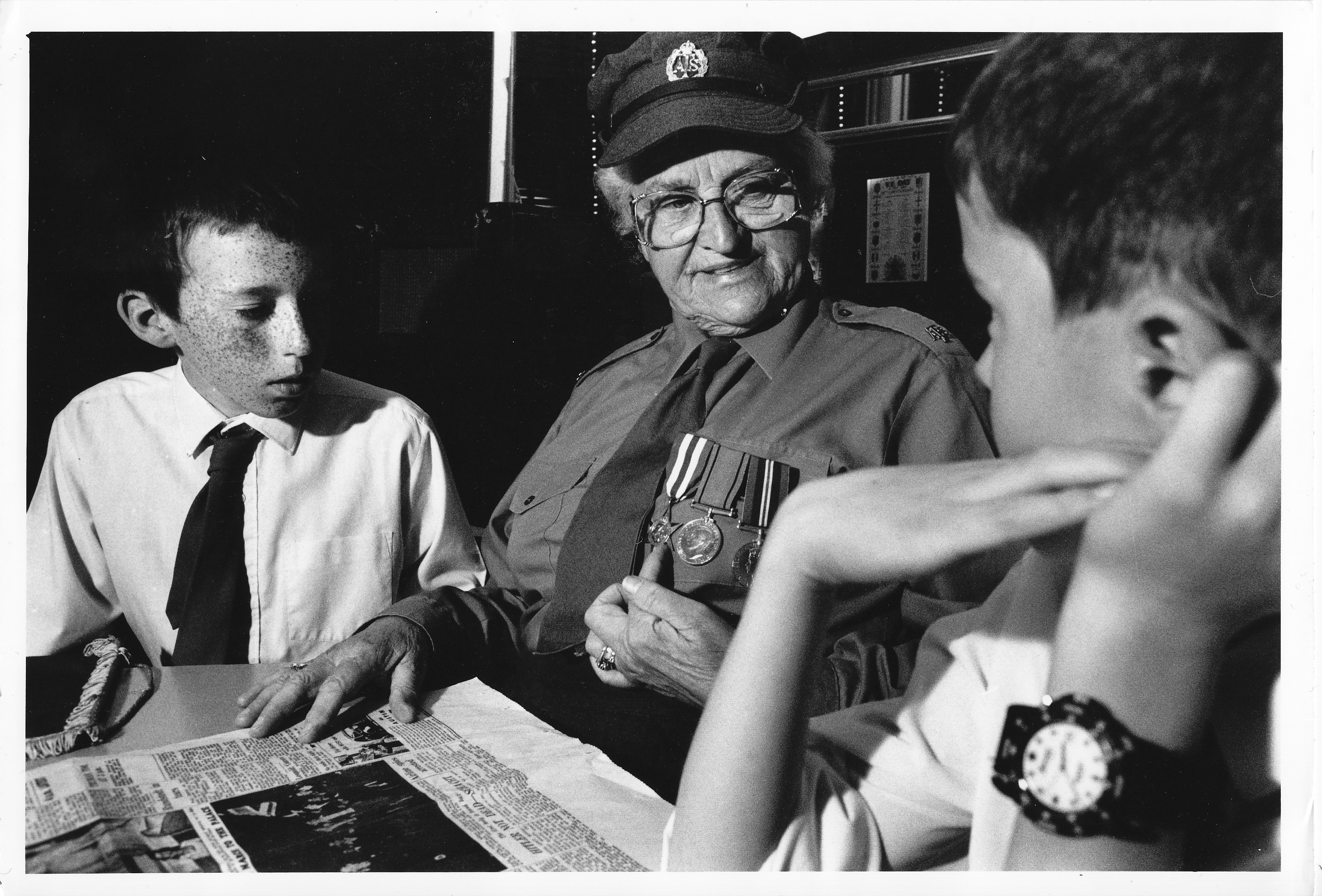 Black and white photograph of school children interviewing a veteran about VE day. Image courtesy of Tim Smith.