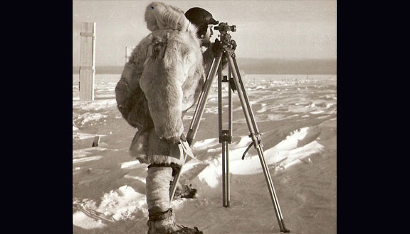 Charles Swithinbank surveys stakes in an ice sheet in Antarctica, early 1950s