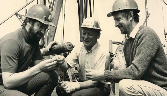 Anthony Laughton and others examining a core of deep sea sediment, late 1960s/early 1970s