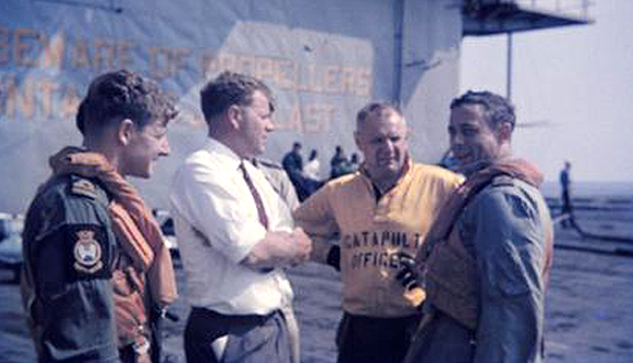 Dennis Higton (in white shirt) talking to Buccaneer air crew on board the USS Lexington